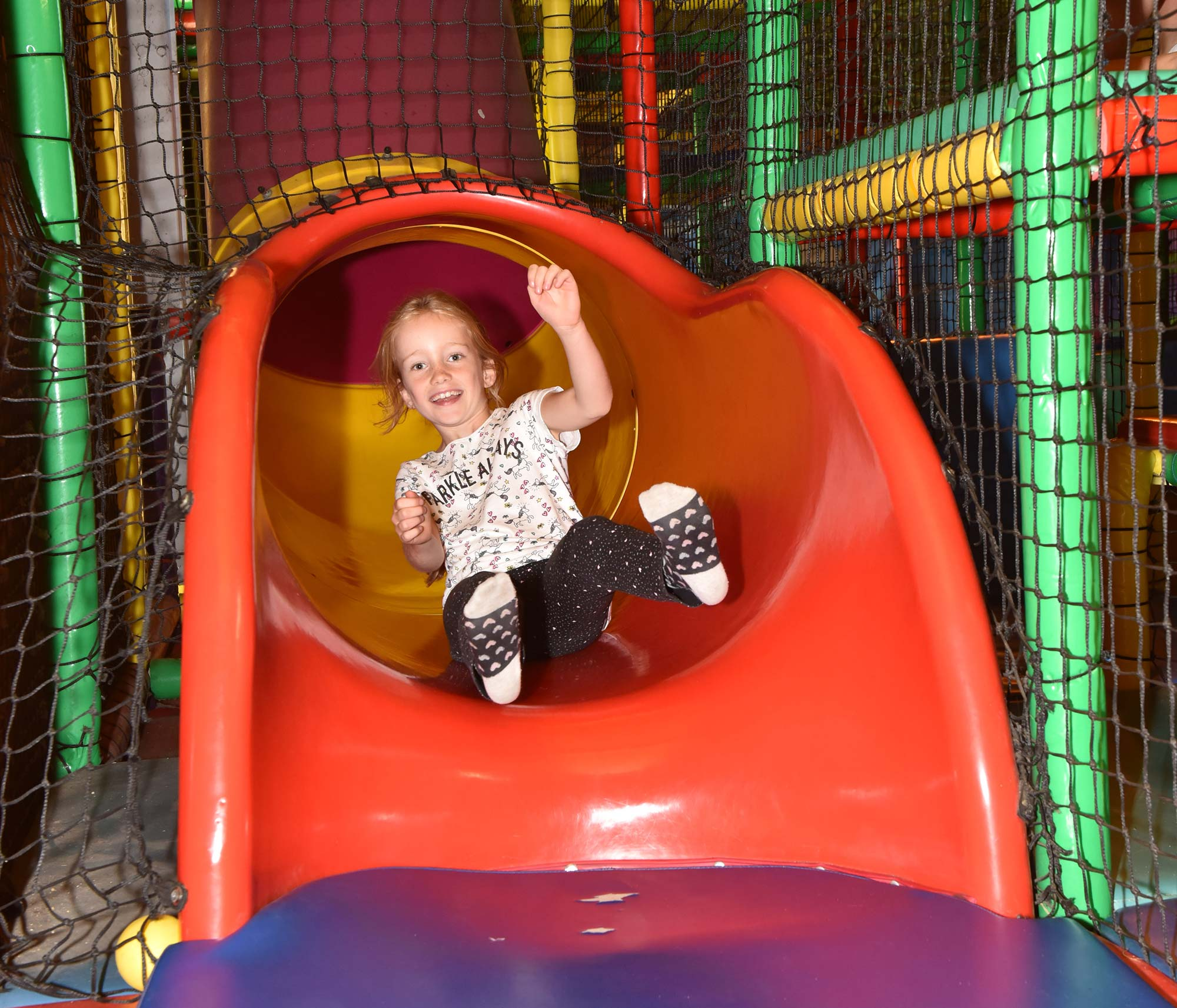 Having fun on a slide in the indoor soft play area at Abbotsbury Children's Farm
